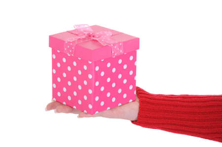 A close up of a female hand holding a pink gift box. A great birthday concept. Isolated on a solid white background.