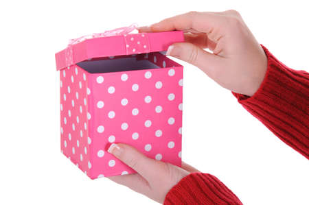 A close up of a woman opening a her gift. A great birthday concept. Isolated on a solid white background.  Foto de archivo
