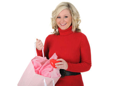 A cute young woman surprised with her gift of a red heart. Isolated on a solid white background.