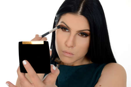 Young woman applying eyeshadow powder, holding small mirror