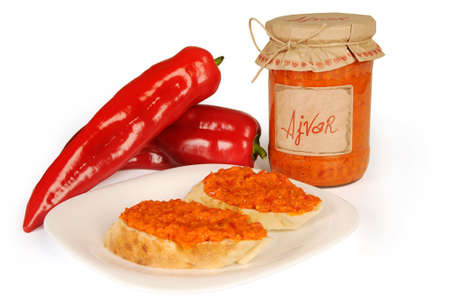 Ajvar, a delicious roasted red pepper and eggplant dish. Serbian and Macedonian traditional dish isolated on white background. Sauce spread on two slices of bread on plate.