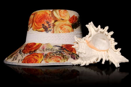 Straw flowery hat and a murex sea shell, isolated on black background Stock Photo