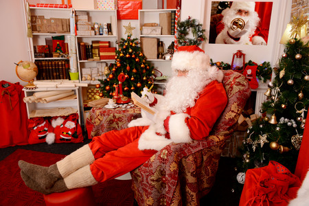 Santa Claus sitting in his wooden house in a comfortable chair and prepare gifts for Christmas. He checks his list in a notebook