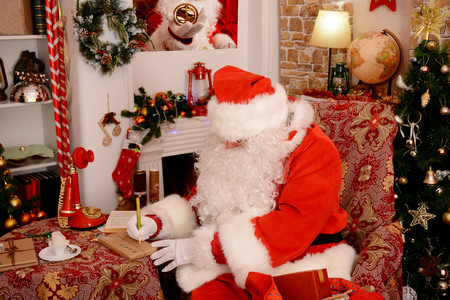 Santa Claus is preparing for Christmas. Santa Claus in a beautiful room next to the fireplace and Christmas tree sits with a sack of gifts