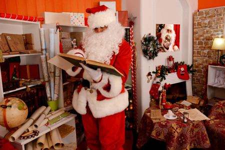 Santa Claus preparing for travel and looking at the world map. He is at home, decorated for Christmas. Stock Photo
