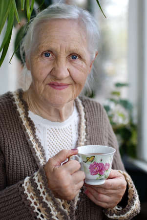 Ältere Patienten, lächelnde Frau mit Tasse Tee auf dem Balkon