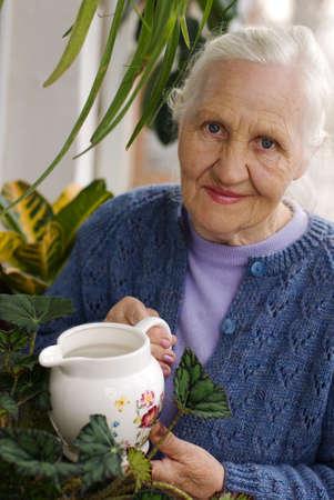 Spring portrait of elderly woman watering her flowers