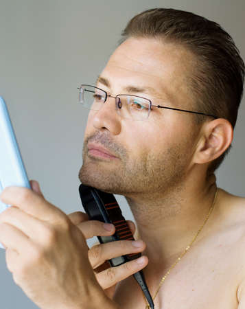 Handsome man shaving with electric razor, looking into mirror Stock Photo