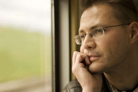 Thinking man looking out of window,  in the train Stock Photo