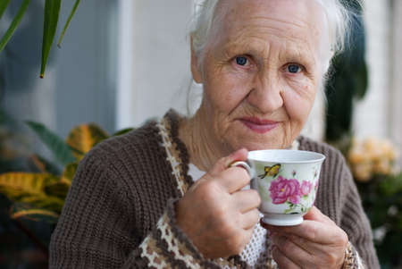 Elderly woman with cup of tea at the balcony