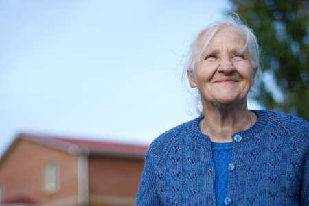 Happy elderly woman, building on the background