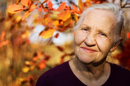 vecchiaia: Ritratto di donna anziana sorridente su sfondo autunnale