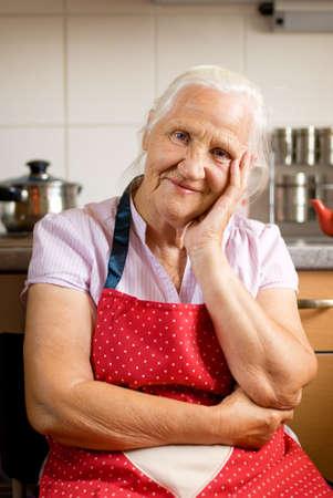 mujeres cocinando: Sonriente mujer de alto nivel en la cocina