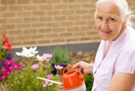 Summer portrait of elderly woman watering her flowers