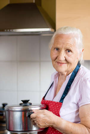 Smiling senior woman in the kitchen is holding a casserole Standard-Bild