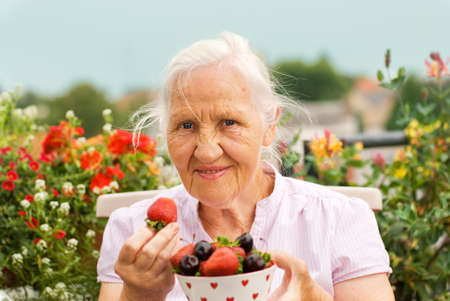Elderly smiling woman sitting on the terrace, holding a bowl with strawberry and cherries photo