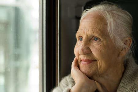 Piękny babcia, patrząc w okno, w pociągu