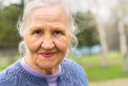 Portret van een lachende oudere vrouw. Een foto op de natuur achtergrond