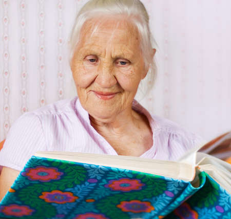 Elderly woman looking at the family photo album