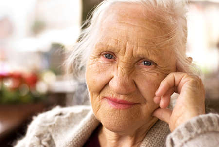 Portrait of the smiling elderly woman, sitting outdoor Stock Photo