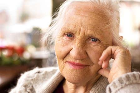 senioren wandelen: Portret van de lachende oudere vrouw, zittend buiten Stockfoto