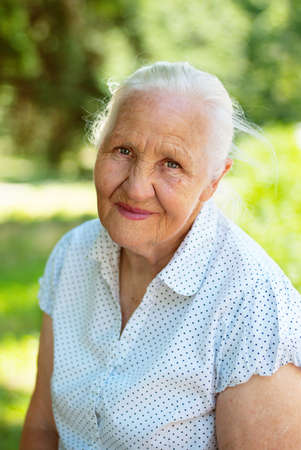 Elderly lovely woman sitting in a park, sunny summer day