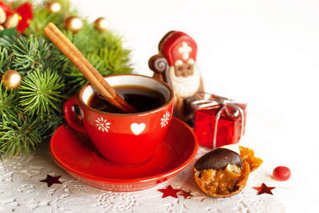 Cup of hot tea with cinamon, with chocolat figurine St  Nicholas and candies