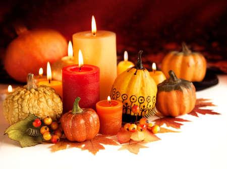 Candle and pumpkins on a autumn background Standard-Bild