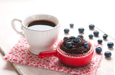 Morning coffee, cupcake with chocolate and blueberry on a table, Blueberry Chocolate Muffin photo