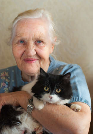 Smiling happy elderly woman with her cat. Selective focus on a cat