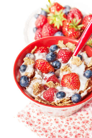 wildberry: A bowl of cereals with blueberries, strawberries and raspberries with yogurt on a table, healthy breakfast