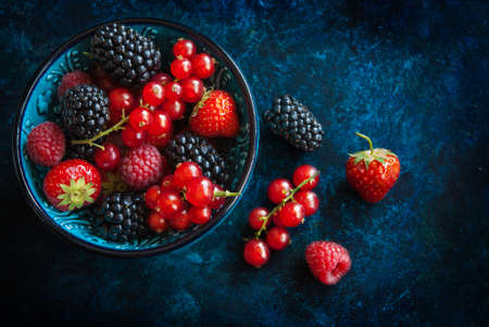 Summer berries in bowl on a table, fruits, raspberry, strawberry, red currant and mulberry photo
