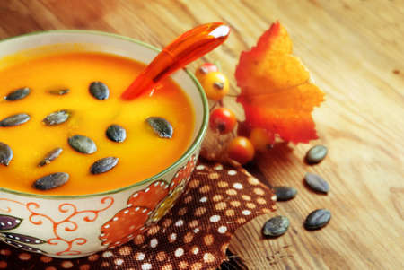 seeps: Autumn pumpkin soup with seeps on a wood table