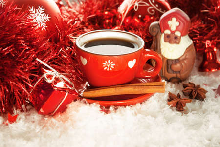Cup of coffee with chocolate Saint Nicholas and gift on a winter background
