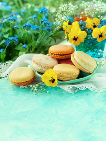 Tasty dessert, macaroons on a table with spring flowers