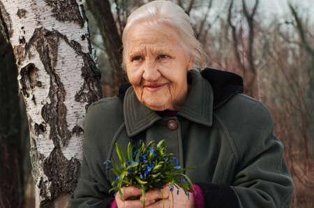 vejez feliz: Retrato del resorte de la anciana sonriente, en un bosque con flores de primavera
