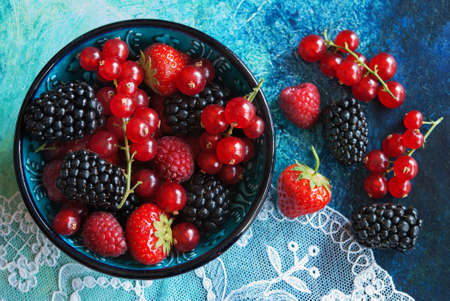wildberry: Summer berries in bowl on a table, fruits, raspberry, strawberry, red currant and mulberry Stock Photo