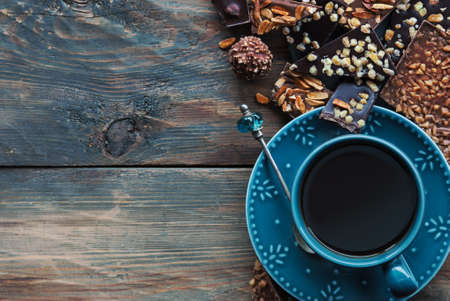 Assortiment of chocolate and cup of coffee on wooden table