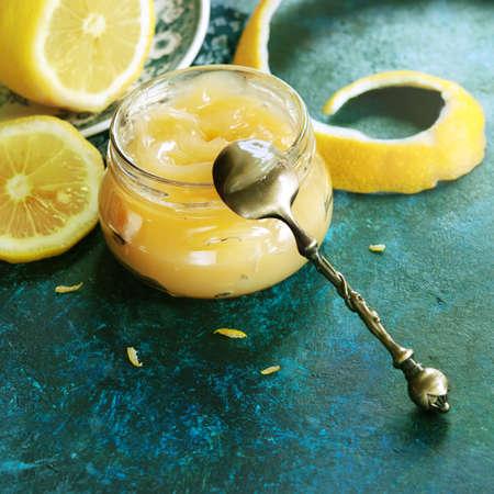 lemon: Homemade lemon curd in glass jar, with fresh lemons (toned picture)