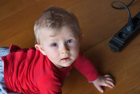 carelessness: Little baby playing with electrical extension on floor at home