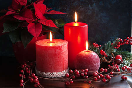 Christmas decor wirh red candles and poinsettia Archivio Fotografico