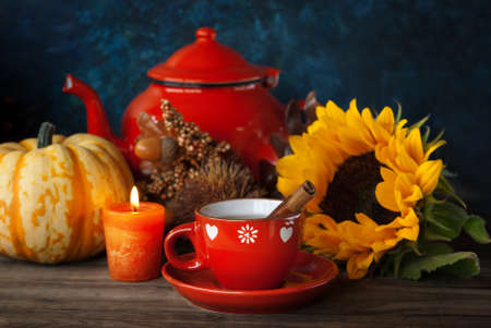 Cup of tea and Autumn thanksgiving decor with candle, sunflower and pumpkin