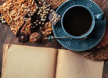 cafe bombon: Taza de café, surtido de chocolates finos negro, chocolate con leche y el libro para las notas sobre la mesa de madera