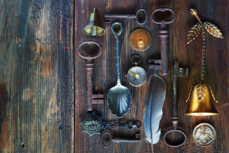 antique background: collection vintage objects. antique keys, clock, compass, bells,wooden background