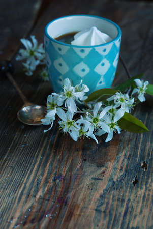 traditinal: A cup of coffee with meringue and spring flowers on a wooden background, selective fokus
