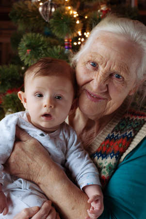 baby near christmas tree: Grandmother and baby toddler, her grandson near Christmas tree, indoor Stock Photo