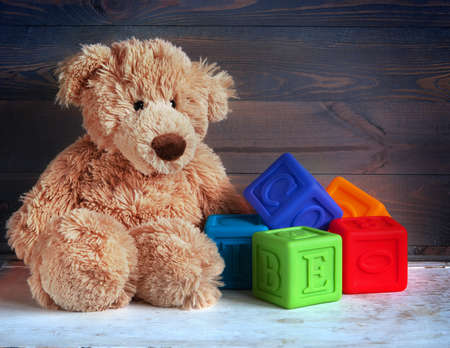 toy bear: Teddy Bear toy and cubes on wood background