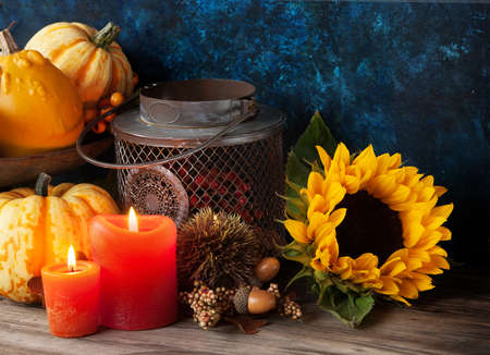 Autumn thanksgiving decor with candle, sunflower and pumpkins