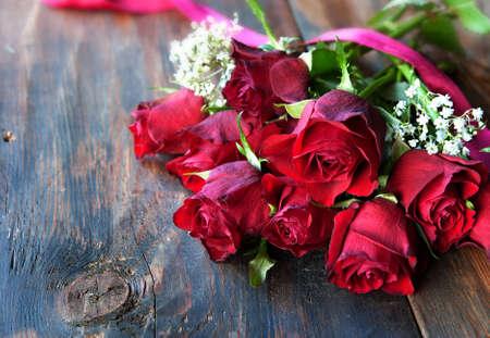 ramo de flores: rosas rojas de San Valentín en el fondo de madera oscura con la cinta roja