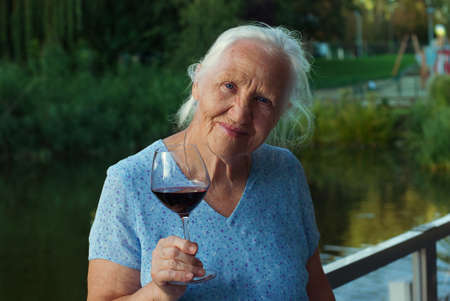 eyes downcast: Happy Elderly woman drinking red wine, outdoors Stock Photo